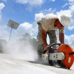 Master Sgt. Donnie Bogan saws cutting lines in concrete
